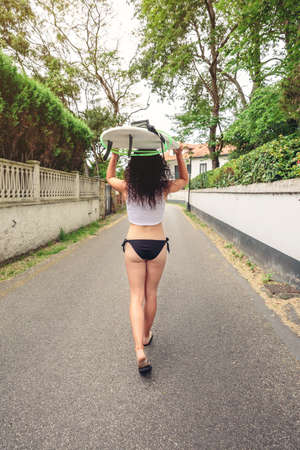 bikini top: Back view of curly brunette girl with white top and black bikini holding surfboard over head and walking on the street. Summer lifestyle concept.