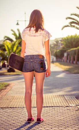 short back: Back view of beautiful young girl with short shorts and skateboard outdoors on a hot summer day. Warm tones edition.