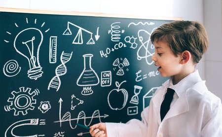atomo: Pequeño científico niño mostrando el dibujo matemática en la pizarra con marcador