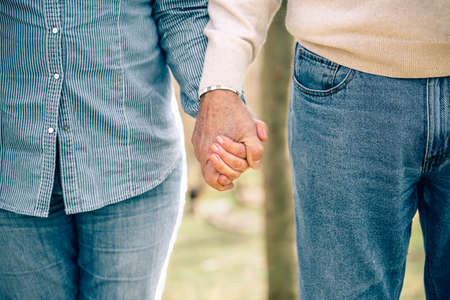 holding close: Close up of senior couple holding hands over nature background