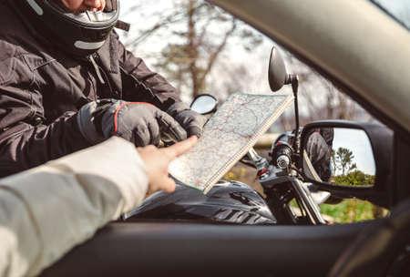 preguntando: motociclista alto pidiendo al conductor del coche de la dirección en la hoja de ruta Foto de archivo