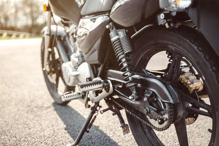shock absorber: Close up shock absorber, chain and disk brake of black shiny motorcycle