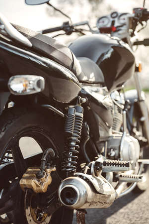 exhaust pipe: Close up shock absorber, exhaust pipe and disk brake of black shiny motorcycle