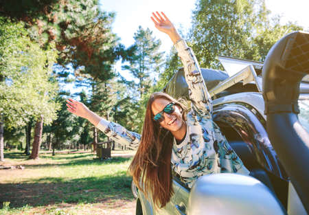 front raise: Portrait of happy young woman raising her arms through the window car in a sunny day over a nature background.