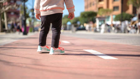 girl shoes: Back view of little girl legs with sneakers and black leggins standing over a city runway on a sunny day Stock Photo
