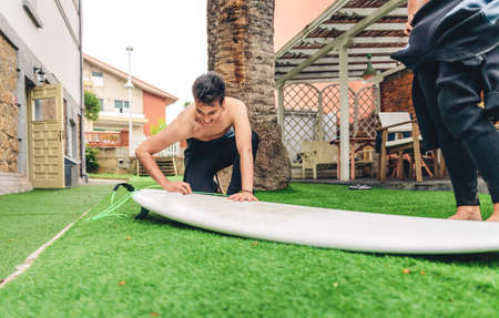 wetsuit: Portrait of surfer man with wetsuit waxing surfboard of a beautiful woman. Summer sports concept.