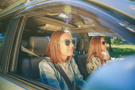 young friends: Happy young women traveling in car in a road trip adventure. Female friendship and leisure time concept.