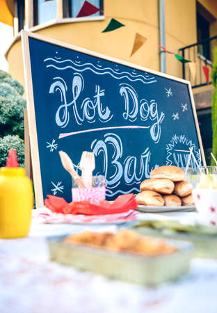 announcing: Blackboard announcing summer party over table with delicious food and drinks ready to take