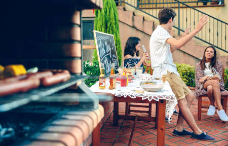 garden barbecue: Young people talking at table in outdoors summer party while sausages are cooking in furnace