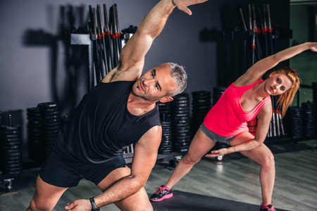 fitness gym: Trainer teaching fitness exercises to young woman in a sports center Stock Photo