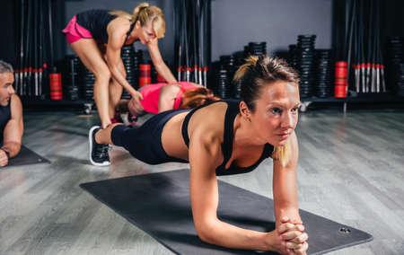 Porträt von Blondinen tuend drücken ups während Trainer, der Position anderer Frau im Hintergrund korrigiert Standard-Bild