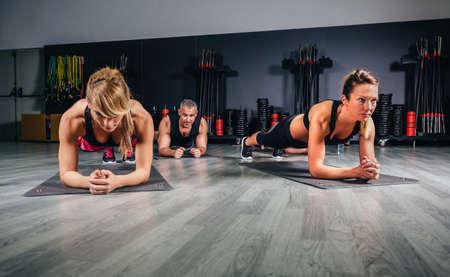Pessoas fazendo flexões na sala de aula de fitness no centro desportivo