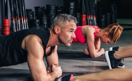 Feche acima do homem fazendo flex�es na sala de aula de fitness no centro desportivo