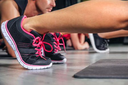 Close up of woman legs with sneakers doing exercises in fitness class