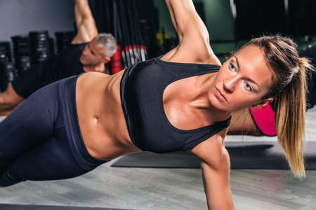 hard core: Portrait of blonde woman with pigtail doing exercises in fitness class