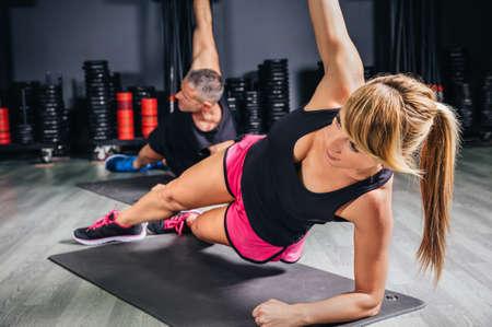 atletismo: Pareja haciendo ejercicios de jóvenes en clase de gimnasia en centro deportivo