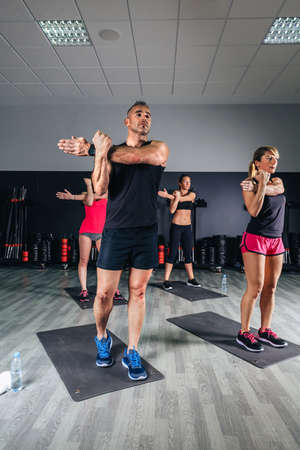 classes: People stretching arms in fitness class on sports center