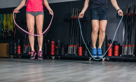 aerobic exercise: People legs doing exercises with jumping ropes in sports center