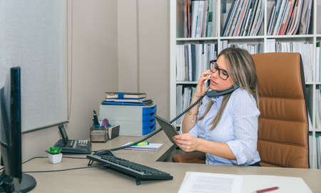 fixed line: Portrait of busy businesswoman talking simultaniously on cell and stationary phone while looking electronic tablet in her hands Stock Photo