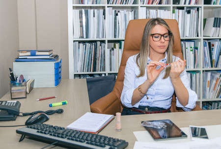 woman in office: Portrait of bored blonde secretary polishing nails at workplace Stock Photo