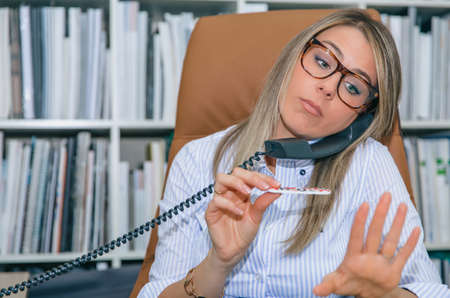 unmotivated: Close up of unmotivated blonde secretary polishing nails at workplace while talking on phone Stock Photo