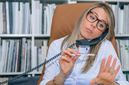 unmotivated: Close up of unmotivated blonde secretary polishing nails at workplace while talking on phone Stock Photo