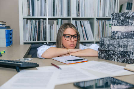 Close up of exhausted blonde secretary looking at folders stack waiting to archive in her desktop