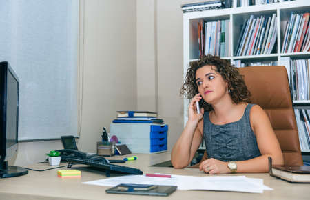 hard working people: Portrait of businesswoman talking with smartphone sitting in office Stock Photo