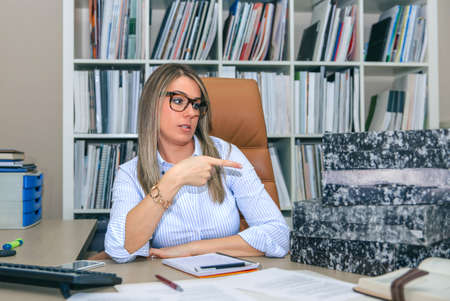 angry blonde: Portrait of angry blonde secretary pointing at folders stack waiting to archive in her desktop Stock Photo