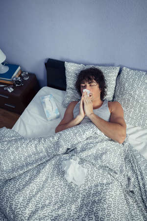 catarrh: Portrait of young man sneezing and covering nose with tissue lying on bed. Sickness and healthcare concept. Stock Photo