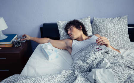 catarrh: Young sick man holding glass of water to take medicines lying on bed. Sickness and healthcare concept.