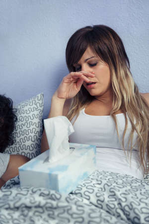 catarrh: Portrait of young sick woman with tissues box sitting on bed. Sickness and healthcare concept.