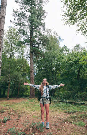 travel woman: Young happy hiker woman with backpack raising her arms and enjoying the forest. Freedom and nature concept.
