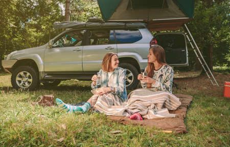 shoes off: Happy young women friends resting sitting under a blanket in campsite into the forest