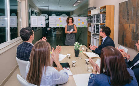 Teamwork applauding to woman chief in a meeting to celebrate success in a business project in headquarters Stockfoto