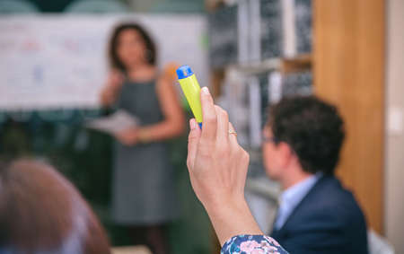 raising: Close up of business woman raising her hand with highlighter to make question in a business meeting