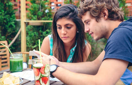 healthy looking: Close up of young couple looking smartphone sitting around of table with healthy drinks in a summer day outdoors Stock Photo