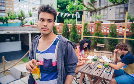 young man portrait: Portrait of young man holding infused water cocktail outdoors with his friends sitting around of table on a summer day