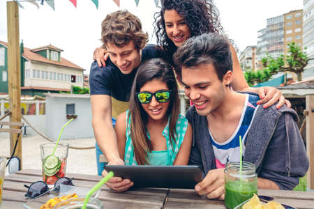 healthy looking: Young happy people looking electronic tablet sitting around of table with healthy drinks in a summer day outdoors. Young people lifestyle concept. Stock Photo