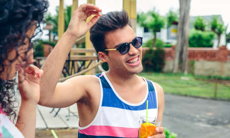 raising: Happy young man with sunglasses laughing and raising his arm while holding beverage in a summer party outdoors. Young people lifestyle concept.