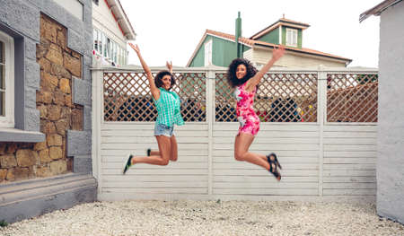 salto de valla: Two happy young women jumping in front of white garden fence