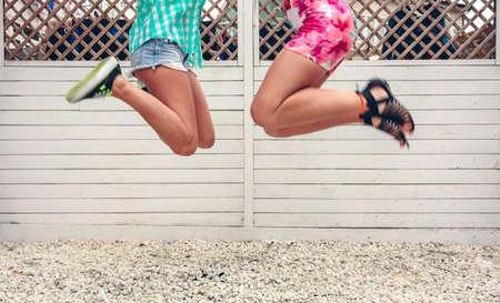 salto de valla: Sección inferior de dos mujeres irreconocibles saltando sobre fondo blanco cerca del jardín