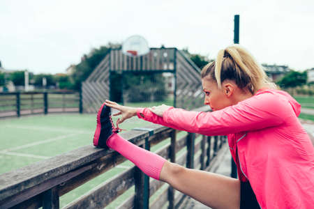 woman stretching: Young blonde woman with pigtail stretching her legs before training outdoors