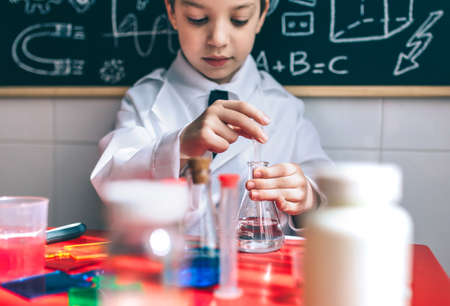 extracting: Portrait of little boy scientist extracting liquid from flask against of chalkboard with drawings. Selective focus on flask. Stock Photo