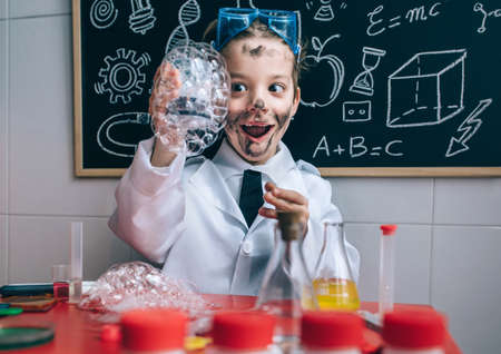 freaks: Portrait of excited little boy scientist with dirty face holding glass with soap foam against of blackboard with drawings
