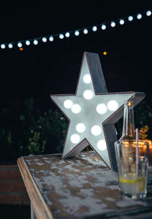 Close up of white handmade star lamp with light bulbs over a wooden table with drinks and lights garland in the background in a outdoors party.