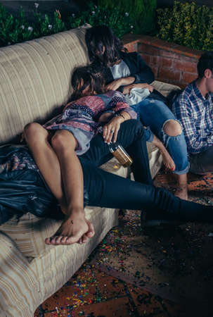 after party: Close up of young drunk friends sleeping in a sofa after outdoors party. Fun and alcohol and drugs problems concept.