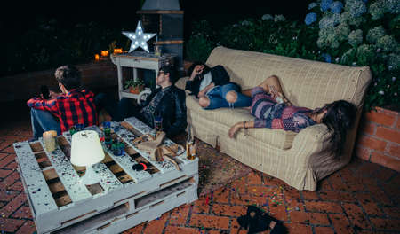 after party: Young drunk friends sleeping in a sofa after outdoors party. Fun and alcohol and drugs problems concept. Stock Photo