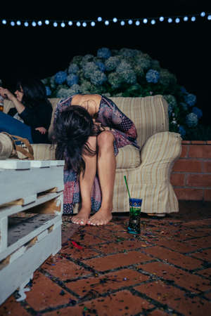 after party: Young drunk woman holding her head sitting in the sofa in a outdoors party. Fun and alcohol and drugs problems concept. Stock Photo
