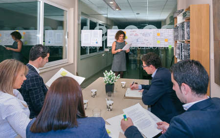 management team: Female coach talking while looking project management to business team sitting at table in headquarters